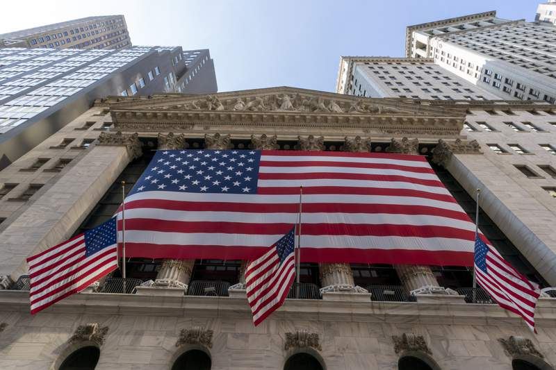 FILE - In this Monday, Sept. 21, 2020, file photo, a giant American Flag hangs on the New York Stock Exchange. U.S. stocks are climbing Monday, Nov. 2, 2020, kicking off a potentially turbulent stretch for markets, as Wall Street recovers some of its sharp sell-off from last week. (AP Photo/Mary Altaffer, File)