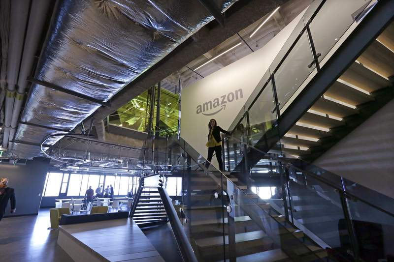 """FILE - In this Sept. 27, 2017, file photo, an Amazon worker walks down steps in a company office before an event announcing several new Amazon products by the company in Seattle. Amazon plans to have its employees return to the office by fall as the tech giant transitions away from the remote work it implemented for many workers due to the coronavirus pandemic. On Tuesday, March 30, 2021, the company told employees it is planning a """"return to an office-centric culture as our baseline."""" (AP Photo/Elaine Thompson, File)"""