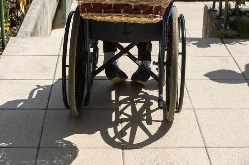 Carmela Bergamelli, 87, sits in a wheelchair as she talks to her family at the Martino Zanchi Foundation nursing home in Alzano Lombardo, Italy, Friday, May 29, 2020. (AP Photo/Luca Bruno)