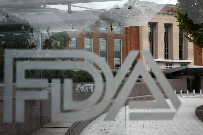 FILE - This Aug. 2, 2018, file photo shows the U.S. Food and Drug Administration building behind FDA logos at a bus stop on the agency's campus in Silver Spring, Md. Health officials reported the first U.S. drug shortage tied to the viral outbreak that is disrupting production in China, but they declined to identify the manufacturer or the product. The Food and Drug Administration said late Thursday, Feb. 27, 2020, that the drug's maker contacted health officials recently about the shortage, which it blamed on a manufacturing issue with the medicine's key ingredient.  (AP Photo/Jacquelyn Martin, File)