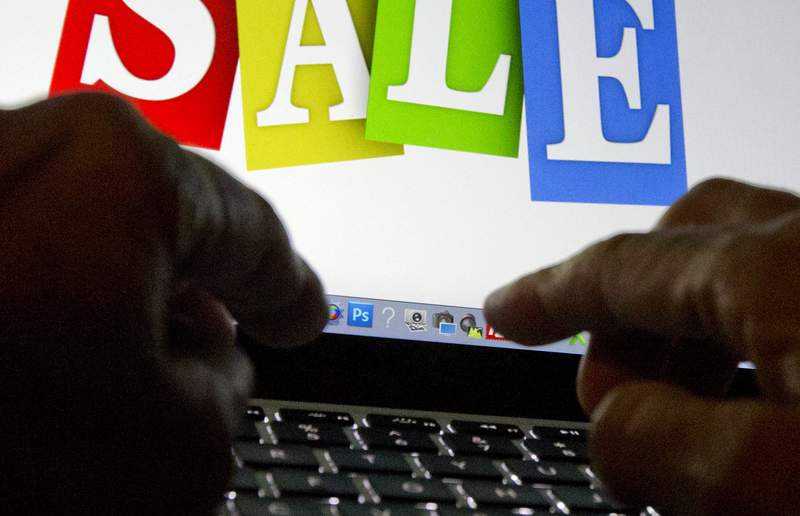 FILE - In this Dec. 12, 2016 file photo, a person in Miami searches the internet for sales. Online shopping scams are on the rise as thieves look to take advantage of the increase in people shopping online during the pandemic.  (AP Photo/Wilfredo Lee, File)