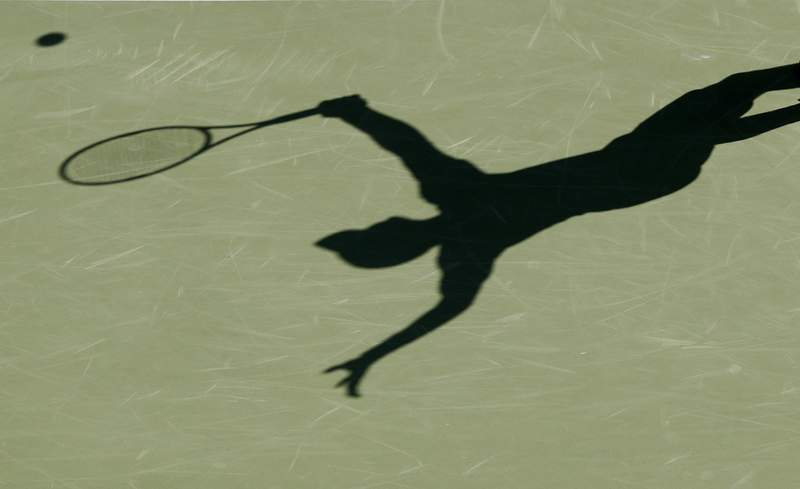 FILE - This is a 2017 file photo showing the shadow of a tennis player. The group charged with monitoring tennis gambling and punishing corruption found a near-doubling in the number of suspect matches in the first three months of 2020 -- an increase it tied to the coronavirus pandemic. (AP Photo/File)