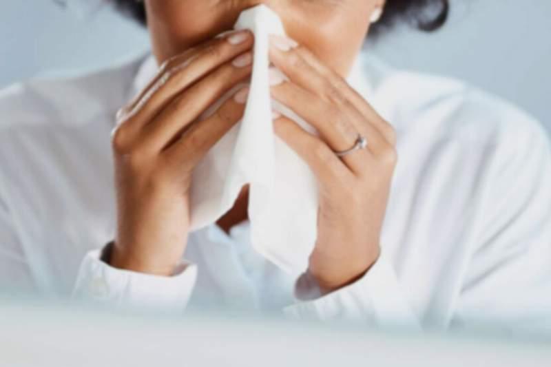 A woman sneezing.