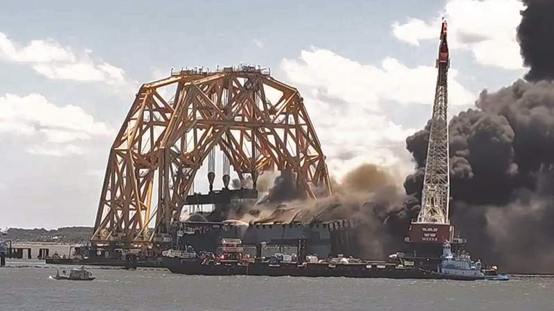 Webcam shows flames and black smoke coming from what's left of the Golden Ray wreckage.