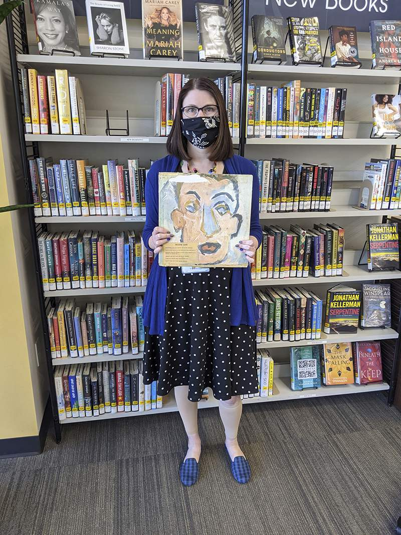"""In this photo provided by Heights Libraries, Sara Phillips, a branch manager with Heights Libraries in Ohio, holds the Bob Dylan double album """"Self Portrait"""" borrowed in 1973 by eighth-grader Howard Simon he returned recently 48 years overdue. (Heights Libraries via AP)"""