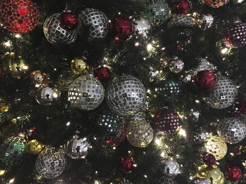 FILE - In this Friday, Dec. 1, 2017, file photo, ornaments hang on a Christmas tree on display in New York. Office holiday parties are tricky in 2020 amid the coronavirus pandemic. Dancing, drinking and fancy dinners are out. Many companies are foregoing parties altogether, deciding instead to send staff gift baskets, extra time off or donations to charities that employees choose. (AP Photo/Swayne B. Hall, File)