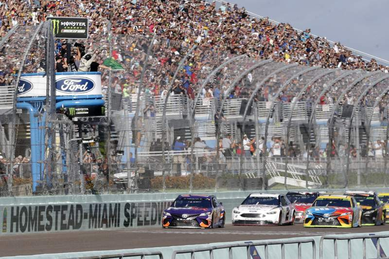FILE - In this Nov. 18, 2018, file photo, Denny Hamlin, left, leads the pack at the start of the NASCAR Cup Series championship auto race at Homestead-Miami Speedway, in Homestead, Fla. NASCAR and IndyCar have each called off their races this weekend. NASCAR was scheduled to run Sunday at Atlanta Motor Speedway without spectators but said Friday, March 13, 2020, it is calling off this weekend and next weeks race at Homestead-Miami Speedway. IndyCar was scheduled to open its season Sunday on the streets of St. Petersburg, Florida, but suspended its season through the end of April. (AP Photo/Lynne Sladky, File)
