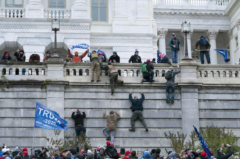 FILE - In this Jan. 6, 2021, file photo, supporters of President Donald Trump climb the west wall of the the U.S. Capitol in Washington. Although pro-democracy and human rights activists around the globe were stunned to see a mob storm the Capitol, they say they were heartened and inspired because the system ultimately prevailed. (AP Photo/Jose Luis Magana File)