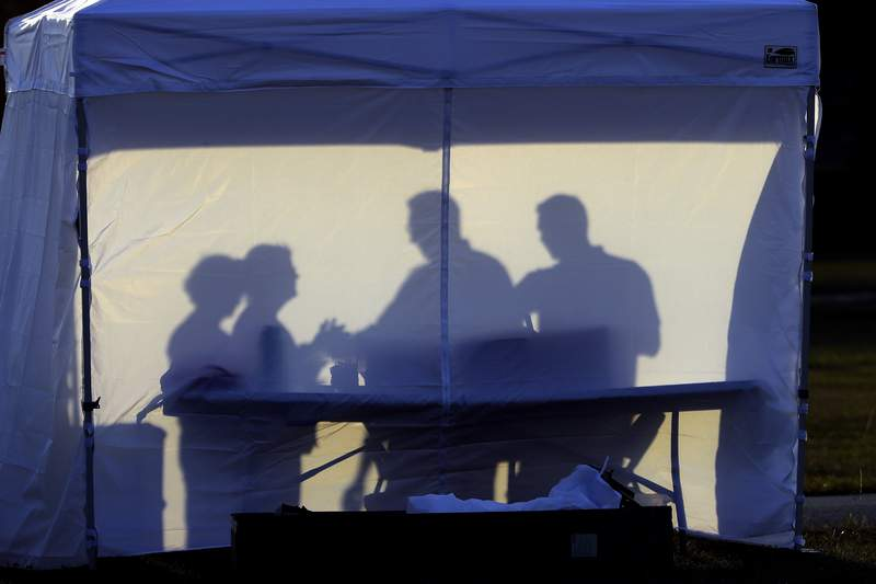 FILE - In this Wednesday, March 25, 2020 file photo, medical personnel are silhouetted against the back of a tent before the start of coronavirus testing in the parking lot outside of Raymond James Stadium in Tampa, Fla. As cases skyrocket in the U.S. and Europe, its becoming more clear that how healthy you were before the pandemic began plays a key role in how you fare regardless of how old you are. (AP Photo/Chris O'Meara)