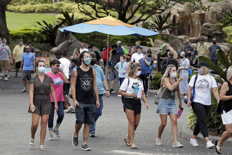 Guests wearing masks stroll through SeaWorld as it reopened with new safety measures in place Thursday, June 11, 2020, in Orlando, Fla. The park had been closed since mid-March to stop the spread of the new coronavirus. (AP Photo/John Raoux)