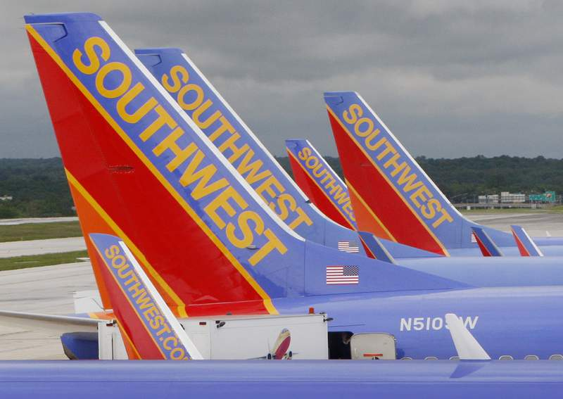 FILE - In this May 16, 2008 file photo, Southwest Airlines jets are seen parked at their gates at Baltimore Washington International Airport in Baltimore, Md. Southwest Airlines will reduce flights for the rest of the year as it tries to restore an operation that stumbled over the summer and now faces lower demand because of the rise in coronavirus cases. Southwest said Thursday, AUg. 26, 2021 it will cut its September schedule by 27 flights a day, or less than 1%, and chop 162 flights a day, or 4.5% of the schedule, from early October through Nov. 5. (AP Photo/Charles Dharapak, file)