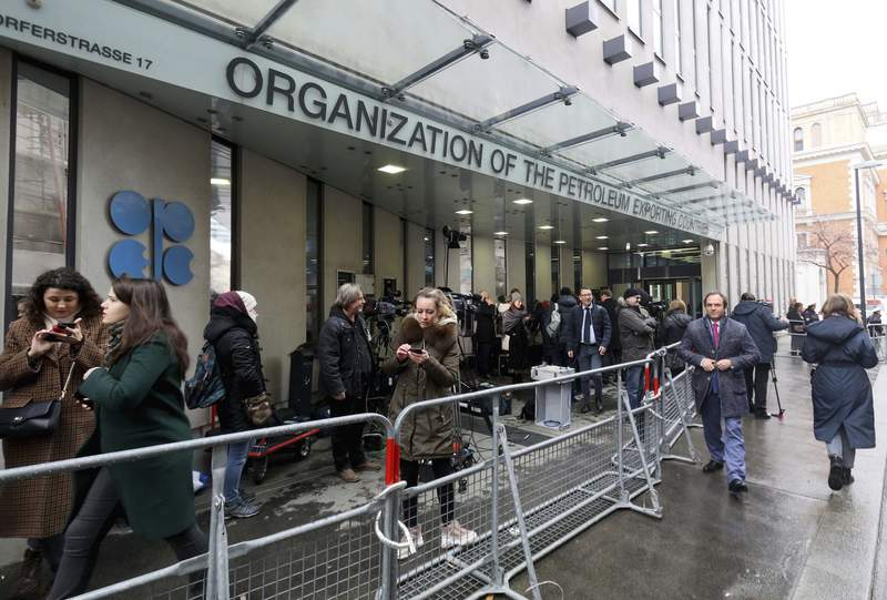 FILE - In this Friday March 6, 2020 file photo, people stand outside the headquarters of the Organization of the Petroleum Exporting Countries, OPEC, in Vienna, Austria. Members of the OPEC oil producing cartel and allied countries led by Russia signed off Wednesday Sept. 1, 2021, on gradually increasing production as the global economy and demand for fuel continue to recover from the worst of the coronavirus pandemic. (AP Photo/Ronald Zak, file)