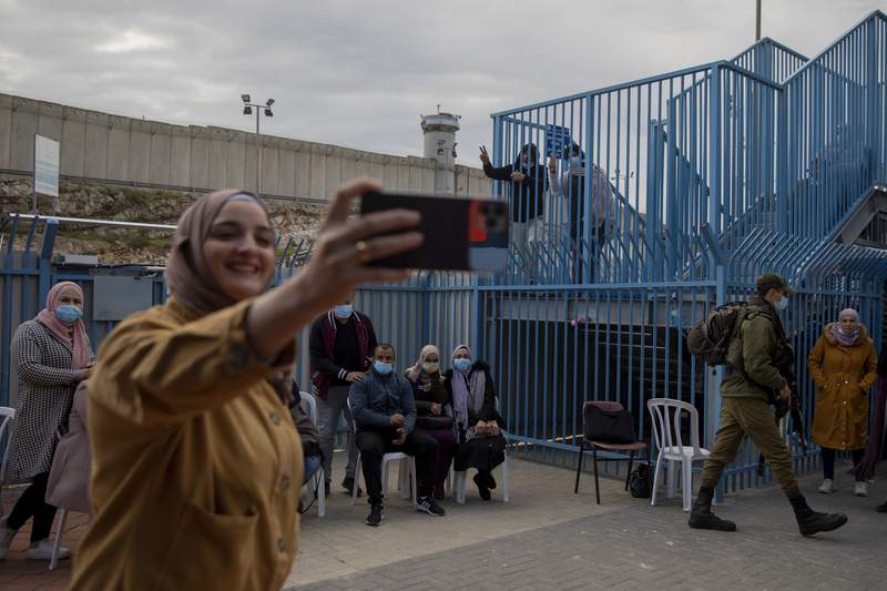 FILE - In this Feb. 23, 2021, file photo, Palestinians take a selfie after receiving the coronavirus vaccine from an Israeli medical team at the Qalandia checkpoint between the West Bank city of Ramallah and Jerusalem. Israel said Friday, June 18, 2021 it will transfer around 1 million doses of soon-to-expire coronavirus vaccines to the Palestinian Authority in exchange for a similar number of doses the Palestinians expect to receive later this year. (AP Photo/Oded Balilty, File)