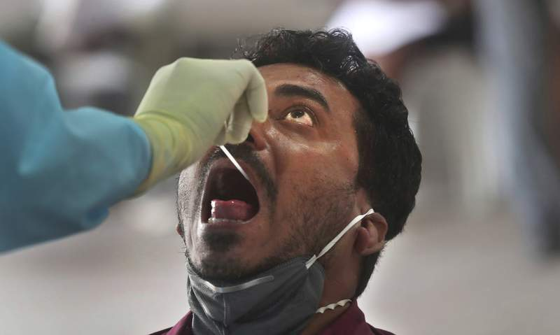 An Indian doctor conducts a swab test of a journalist during lockdown to control the spread of the new coronavirus in Mumbai, India, Thursday, April 16, 2020. Indian Prime Minister Narendra Modi on Tuesday extended the world's largest coronavirus lockdown to head off the epidemic's peak, with officials racing to make up for lost time. (AP Photo/Rafiq Maqbool)