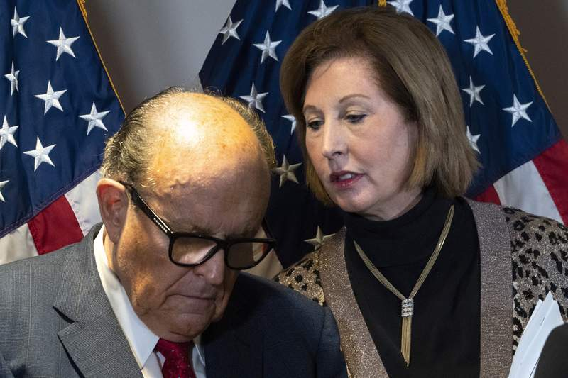 Former Mayor of New York Rudy Giuliani, left, listens to Sidney Powell, both lawyers for President Donald Trump, during a news conference at the Republican National Committee headquarters, Thursday Nov. 19, 2020, in Washington. (AP Photo/Jacquelyn Martin)