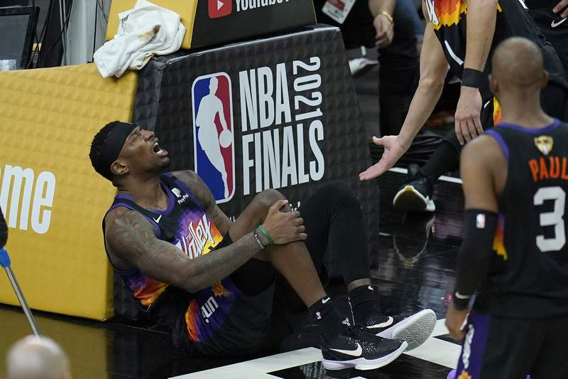 Phoenix Suns forward Torrey Craig grabs his leg during the second half of Game 2 of basketball's NBA Finals against the Milwaukee Bucks, Thursday, July 8, 2021, in Phoenix. (AP Photo/Ross D. Franklin)