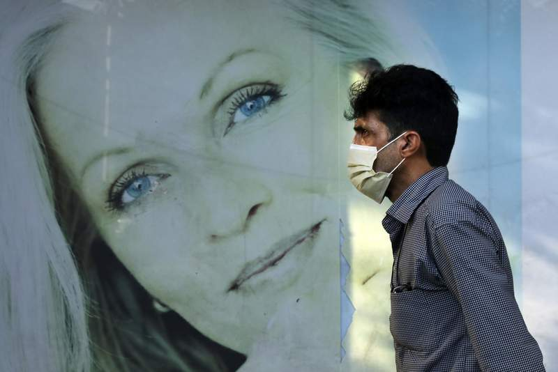 A man wearing protective face mask to help prevent the spread of the coronavirus walks past an advertisement of skin care products in southern Tehran, Iran, Tuesday, July 20, 2021. Iran on Tuesday broke another record in the country's daily new coronavirus cases, even as Tehran and its surroundings went into lockdown, a week-long measure imposed amid another surge in the pandemic. (AP Photo/Vahid Salemi)