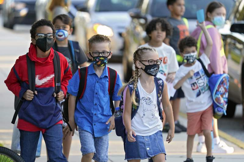 FILE - In this Tuesday, Aug. 10, 2021, file photo, students, some wearing protective masks, arrive for the first day of school at Sessums Elementary School in Riverview, Fla. The on-again, off-again ban imposed by Republican Gov. Ron DeSantis to prevent mandating masks for Florida school students is back in force. The 1st District Court of Appeal ruled Friday, Sept. 10, that a Tallahassee judge should not have lifted an automatic stay two days ago that halted enforcement of the mask mandate ban. (AP Photo/Chris O'Meara, File)