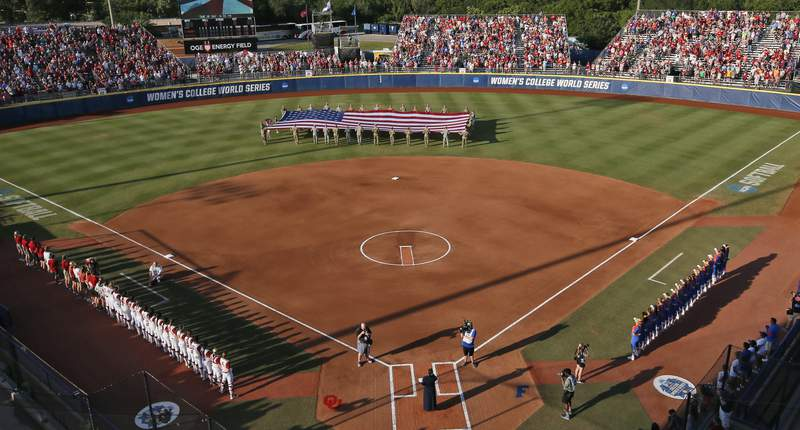 FILE - A large flag is unfurled in the outfield before the second game of the best-of-three championship series between Florida and Oklahoma in the NCAA Women's College World Series in Oklahoma City, in this Tuesday, June 6, 2017, file photo. The NCAA has reached a delicate moment: It must decide whether to punish states that have passed laws limiting the participation of transgender athletes by barring them from hosting its softball and baseball tournaments. (AP Photo/Sue Ogrocki, File)