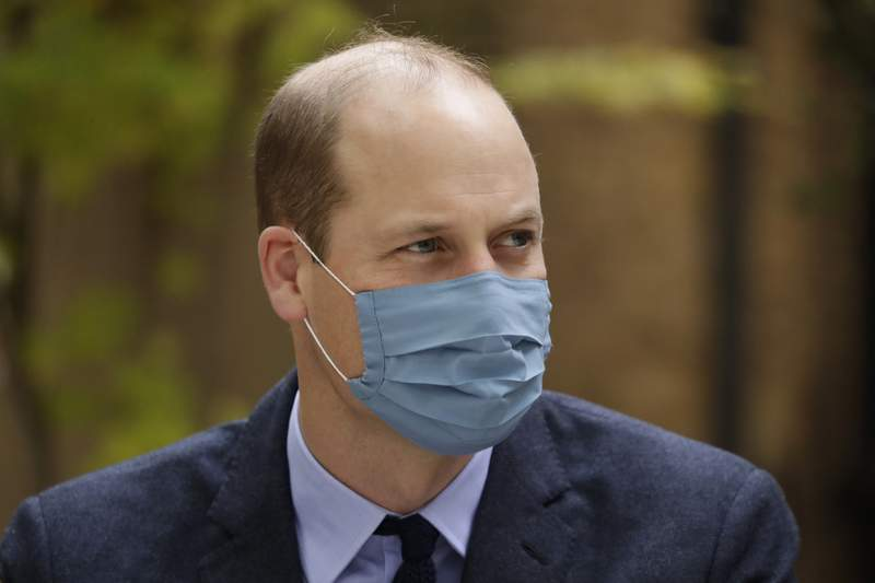 """FILE - In this Oct. 20, 2020, file photo, wearing a face covering to curb the spread of coronavirus Britain's Prince William meets pharmacist Joyce Duah as he and his wife Kate the Duchess of Cambridge visit St. Bartholomew's Hospital in London, to mark the launch of the nationwide """"Hold Still"""" community photography project. Prince William tested positive for the coronavirus, apparently around the same time as his father Prince Charles earlier this year, BBC reported. The report cited unidentified palace sources and The Sun newspaper, which said William kept his telephone and video engagements without revealing his diagnosis because he didn't want to worry anyone. (AP Photo/Matt Dunham, Pool, File)"""