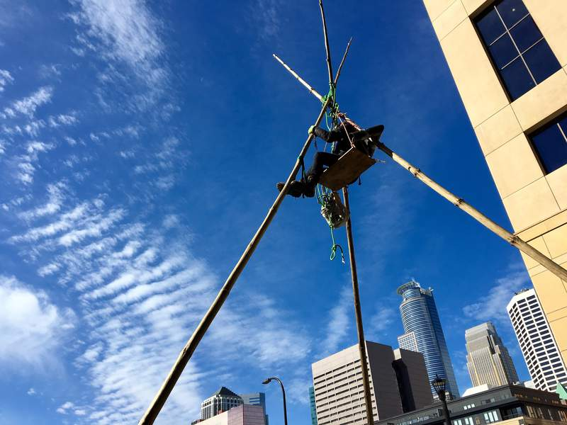 FILE - In this Oct. 4, 2018 file photo, a protester is suspended at the top of a tepee erected outside Wells Fargo in downtown Minneapolis during a protest against Enbridge Energy's planned Line 3 replacement crude oil pipeline across northern Minnesota. Environmental and tribal groups opposed to Enbridge Energy's plan to replace its aging Line 3 crude oil pipeline are planning large scale protests with potential arrests Monday, June 7, 2021, as the Canadian-based company gears up for a final construction push. (AP Photo/Jeff Baenen File)