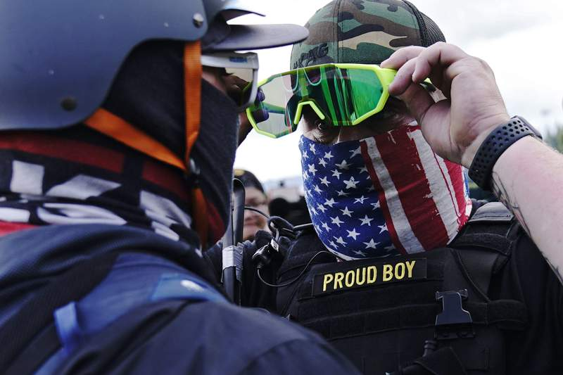 FILE - In this Sept. 26, 2020, file photo, member of the Proud Boys, right, stands in front of a counter protester as members of the Proud Boys and other right-wing demonstrators rally, in Portland. In its annual report set to be released Monday, Feb. 1, 2021, the Southern Poverty Law Center said it identified 838 active hate groups operating across the U.S. in 2020. (AP Photo/John Locher, File)
