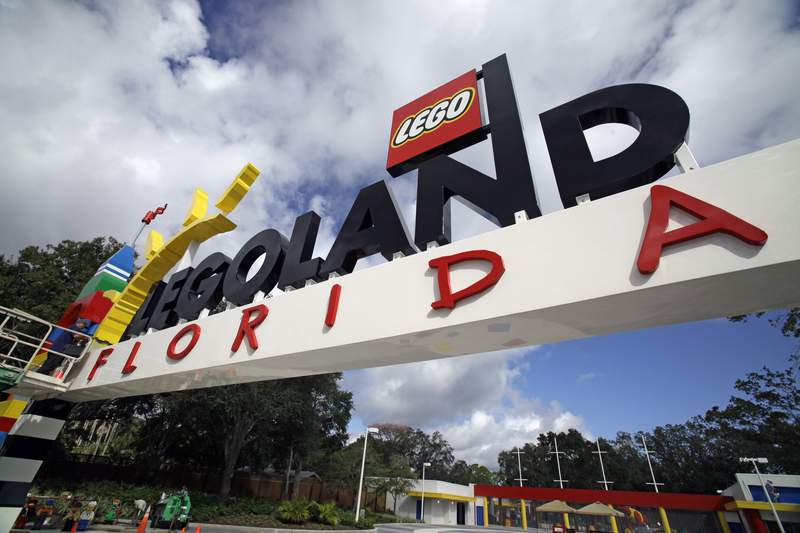 FILE - In this Tuesday, Sept. 27, 2011, file photo, a worker puts finishing touches on the entrance sign at Legoland Florida in Winter Haven, Fla. The Legoland theme park in Florida is planning an expansion next year including new rides, according to plans filed with the city nearest the attraction. The details have not been revealed, but news outlets report Legoland will add about 4.5 acres (1.8 hectares) to its resort near Winter Haven.(AP Photo/John Raoux, File)