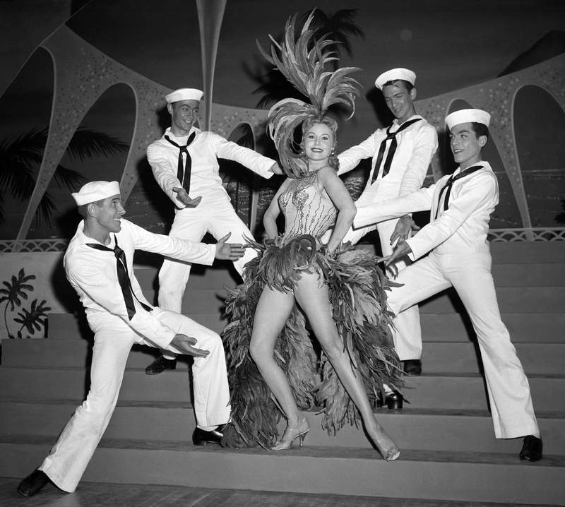FILE - In this May 20, 1957 file photo, Actress Rhonda Fleming blossoms out as a singer and dancer in the first night club appearance of her career at the New Tropicana hotel in Las Vegas.  Actress Rhonda Fleming, the fiery redhead who appeared with Burt Lancaster, Kirk Douglas, Charlton Heston, Ronald Reagan and other film stars of the 1940s and 1950s, has died, Wednesday, Oct. 14, 2020. She was 97.(AP Photo/David Smith, File)