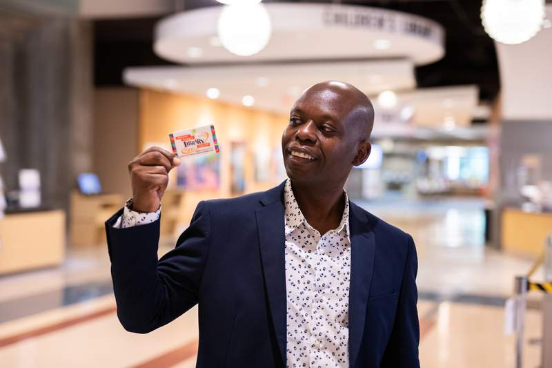 A man holds up his library card.