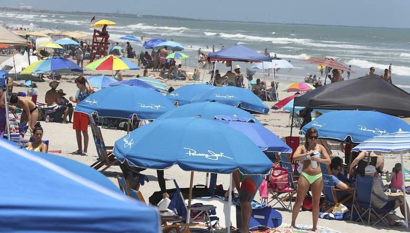 Cocoa Beach, Fla., is packed with Memorial Day beachgoers on Saturday, May 23, 202 The beaches are open for business again during the coronavirus epidemic. (Stephen M. Dowell/Orlando Sentinel via AP)