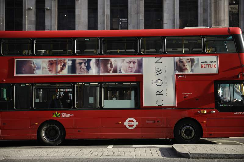 """A traditional double decker red bus with an advert for """"The Crown"""" drives through central London, Tuesday, Dec. 1, 2020. Britain's Culture Secretary Oliver Dowden in a newspaper interview published Sunday Nov. 29, 2020, said he thinks """"The Crown"""" should come with a disclaimer as it's a work of fiction with historical liberties taken in the Netflix drama about the British royal family. (AP Photo/Matt Dunham)"""
