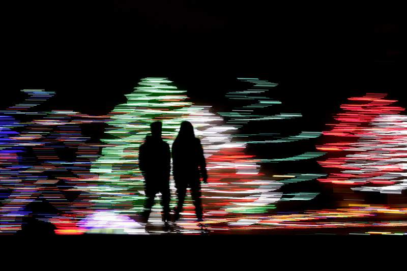 FILE -In this Dec. 12, 2019 file photo taken with a long exposure, people are silhouetted against a Christmas display, at a park in Lenexa, Kan. Most Americans say the holiday season makes them feel very grateful and generous  but many report feeling stressed, too according to a new poll from The Associated Press-NORC Center for Public Affairs Research. (AP Photo/Charlie Riedel, File)