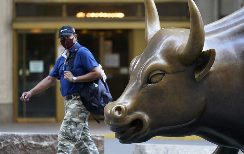 A man wearing a mask passes the Charging Bull statue in New York's financial district, Tuesday, Sept. 8, 2020. More sharp declines for big tech stocks are dragging Wall Street toward a third straight loss on Tuesday. (AP Photo/Mark Lennihan)