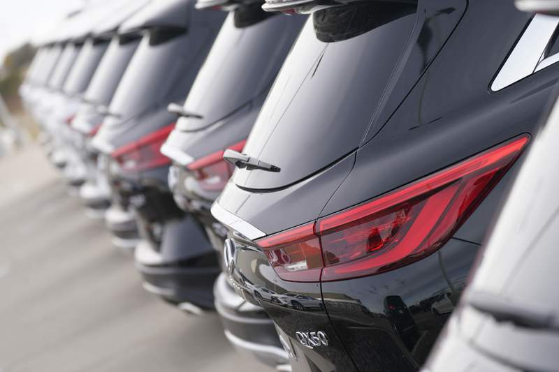 A long row of unsold 2021 QX50 sports-utility vehicles sits at an Infiniti dealership Sunday, Dec. 27, 2020, in Highlands Ranch, Colo.  U.S. auto sales are expected to be down only about 15% for the year, with the average price hitting a record high as sales bounced back during the second half of the year.  AP Photo/David Zalubowski)