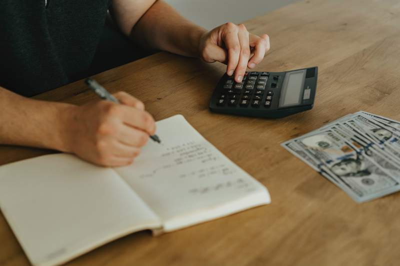 A man sits at a table working on expenses.