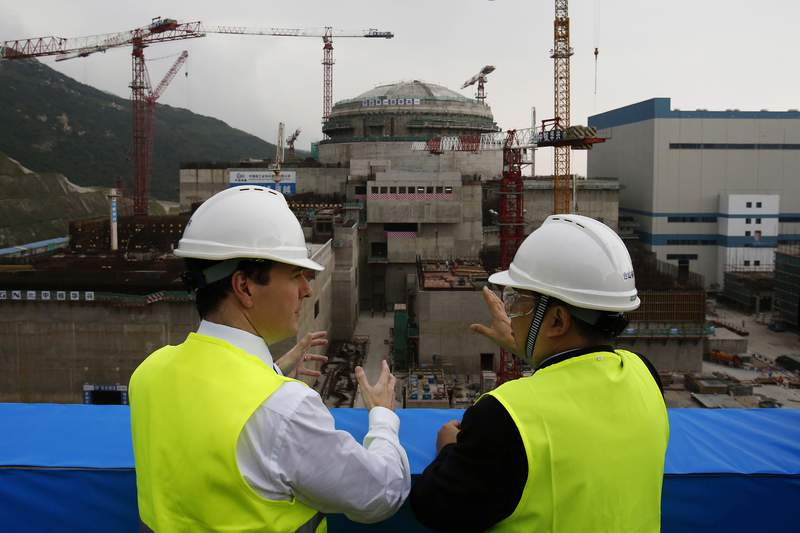 FILE - In this Oct. 17, 2013, file photo, then British Chancellor of the Exchequer George Osborne, left, chats with Taishan Nuclear Power Joint Venture Co. Ltd. General Manager Guo Liming as he inspects a nuclear reactor under construction at the nuclear power plant in Taishan, southeastern China's Guangdong province. The French joint operator of the Chinese nuclear plant near Hong Kong said Monday it is dealing with a performance issue but is currently operating within safety limits, following a report of a potential radioactive leak. (AP Photo/Bobby Yip, Pool, File)