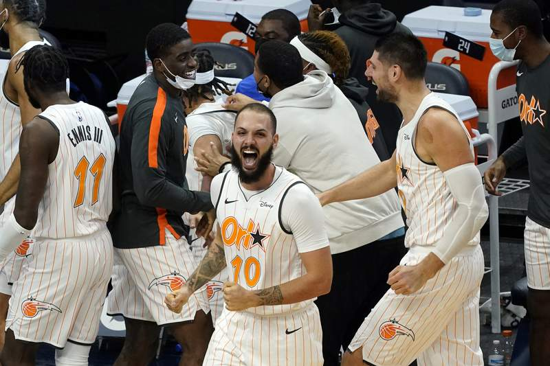 Orlando Magic's Evan Fournier (10) celebrates the game-winning basket by Cole Anthony at the end of an NBA basketball game against the Minnesota Timberwolves, Wednesday, Jan. 20, 2021, in Minneapolis. The Magic won 97-96. (AP Photo/Jim Mone)