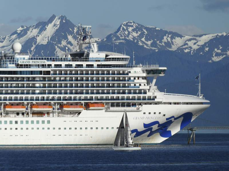In this photo taken Wednesday, May 30, 2018, a sail boat maneuvers near a large cruise ship near Juneau, Alaska. Congress has voted to let large cruise ships sail directly from Washington state to Alaska without stopping in Canada, a step that could clear the way for cruises later this year. The legislation approved by the House on Thursday, May 20, 2021 goes to President Joe Biden, who is expected to sign it. (AP Photo/Becky Bohrer, file)