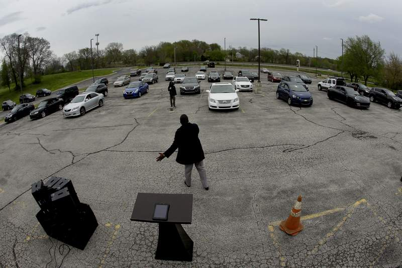 FILE - In this April 12, 2020 file photo, Pastor W.R. Starr II preaches during a drive-in Easter Sunday service while churchgoers listen from their cars in the parking lot at Faith City Christian Center in Kansas City, Kan. As states grapple with when and how to reopen establishments amid the coronavirus pandemic, churches and nonprofits across the country are defending their religious freedom in court, finding success in the less polarizing practice of a drive-in worship designed to gather the faithful in person, at a distance. (AP Photo/Charlie Riedel, File)