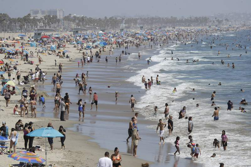 Visitors crowd the beach Sunday, July 12, 2020, in Santa Monica, Calif., amid the coronavirus pandemic. A heat wave has brought crowds to California's beaches as the state grappled with a spike in coronavirus infections and hospitalizations. (AP Photo/Marcio Jose Sanchez)