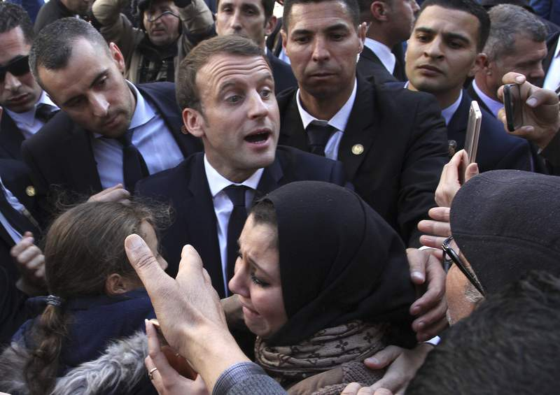 """FILE- In this Dec.6, 2017 file photo, French President Emmanuel Macron meets residents in Algiers. Algeria has announced the immediate recall of its ambassador from Paris in a burst of fury over what it said were """"inadmissible"""" comments attributed to French President Emmanuel Macron. (AP Photo/Anis Belghoul, File)"""