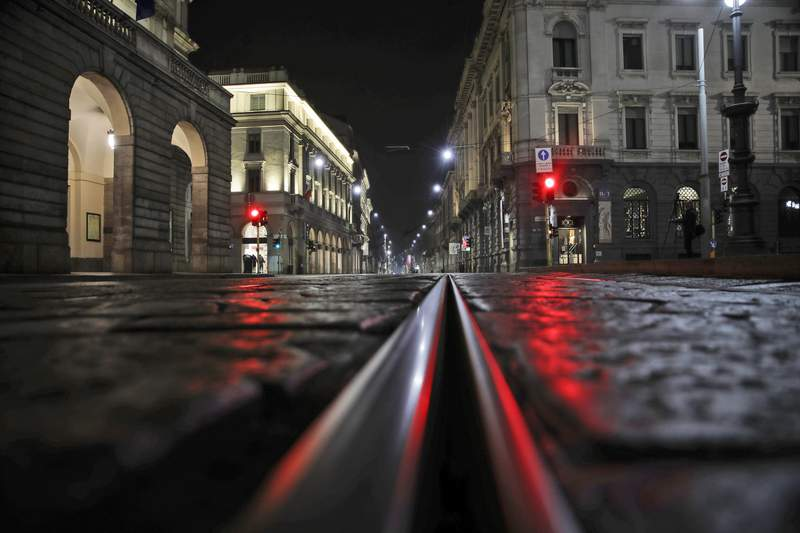 FILE - In this Sunday, Oct. 25, 2020 file photo, an empty street in front of La Scala opera house, left, is illuminated by a red traffic light in Milan, Italy. After a rash of COVID-19 infections among musicians and chorus members, the Dec. 7 season premiere at Milans La Scala opera house, a gala event that is one of Italys cultural highlights, is being canceled. The theaters board of directors on Wednesday concluded that the pandemics situation and Italys anti-COVID-19 measures, which include closure of theaters until at least Nov. 24, wont allow for achieving a production open to the public and of the level and with the characteristics required  for the premiere. (AP Photo/Luca Bruno, File )