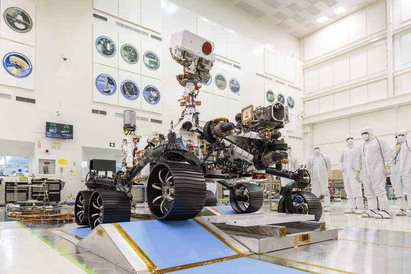 """In this Dec. 17, 2019 photo made available by NASA, engineers watch the first driving test for the Mars 2020 rover in a clean room at the Jet Propulsion Laboratory in Pasadena, Calif. On Thursday, March 5, 2020, NASA announced the explorer's name will be """"Perseverance."""" (J. Krohn/NASA via AP)"""