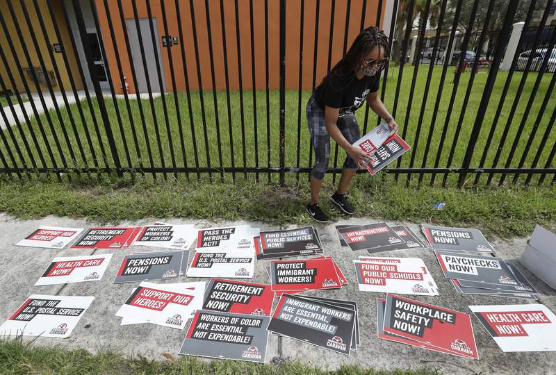 Kelli Ann Thomas, a candidate for Community Council, sorts signs before the start of a Workers First Caravan, Wednesday, June 17, 2020, in Miami. The caravan was part of a nation-wide effort to urge those in government to implement policies that further economic and racial justice. (AP Photo/Wilfredo Lee)