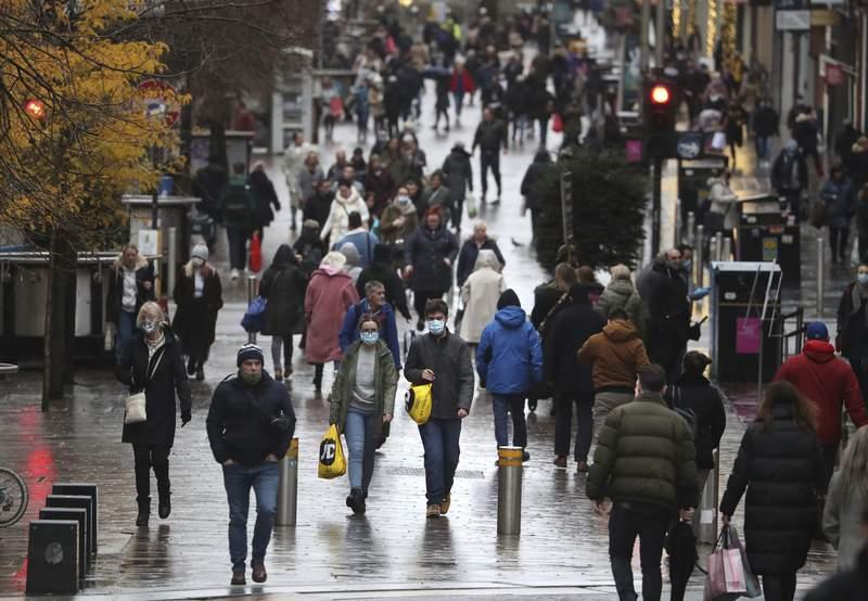 People walk along Buchanan Street in Glasgow, Scotland, Tuesday Nov. 17, 2020. (Andrew Milligan/PA via AP)