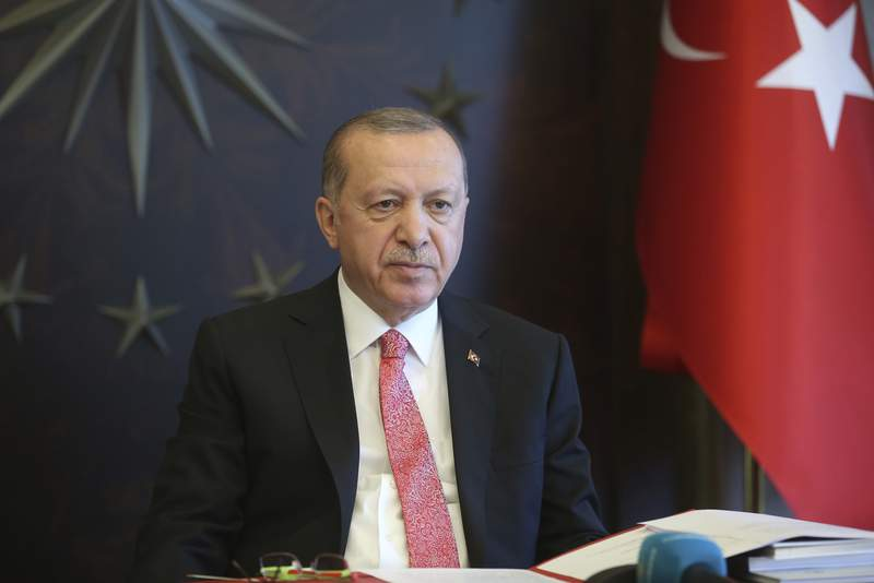 Turkish President Recep Tayyip Erdogan, listens during a teleconference with his cabinet in Istanbul, Monday, May 11, 2020. Erdogan announced a new four-day curfew to stem infections, that includes the weekend and a public holiday on May 19. The country has opted to impose short weekend curfews, instead of full lockdowns, fearing their possible negative effects on the already troubled economy.(Presidential Press Service via AP, Pool)