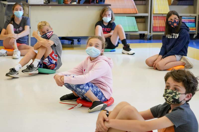 FILE - In this May 18, 2021 file photo, fifth graders wear face masks are seated at proper social distancing spacing during a music class at the Milton Elementary School in Rye, N.Y.  As more children go back to the physical classroom, families are expected to spend robustly on a wide range of items, particularly  trendy clothing for the critical back-to-school season, according to one key spending measure. (AP Photo/Mary Altaffer, File)