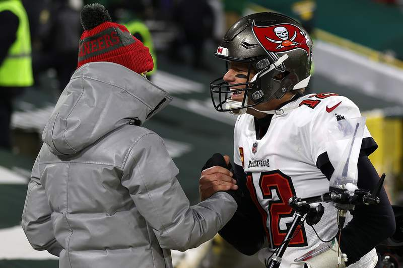 GREEN BAY, WISCONSIN - JANUARY 24: Tom Brady #12 of the Tampa Bay Buccaneers greets his son Jack following their victory over the  Green Bay Packers in the NFC Championship game at Lambeau Field on January 24, 2021 in Green Bay, Wisconsin. The Buccaneers defeated the Packers 31-26.  (Photo by Stacy Revere/Getty Images)