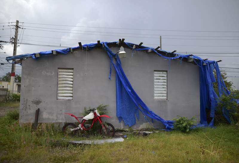 FILE - In this May 28, 2020 file photo, the home of 85-year-old Carmen Lacen, sits inhabitable after the passing of Hurricane Maria partially covered by a torn, blue tarp, in Loiza, Puerto Rico. The U.S. territory is slated to receive more than $6 billion in federal funds to help prepare for future hurricanes and other disasters, officials said Tuesday, Feb. 2, 2021. (AP Photo/Carlos Giusti, File)