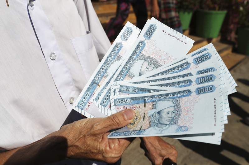 In this Jan. 7, 2020, file photo, a man shows new currency notes outside a bank in Yangon, Myanmar. U.S. and UK sanctions targeting two huge Myanmar military-controlled conglomerates following last month's coup is the most recent attempt to cut them off from dealings with banks and businesses in the United States and United Kingdom. (AP Photo, File)
